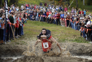 Elliot Storey races through the mud pit while carrying his wife, Giana Storey, both of Westbrook to win the North American Wife Carrying Championship.  They covered the 278-yard obstacle course in 59.18 seconds.