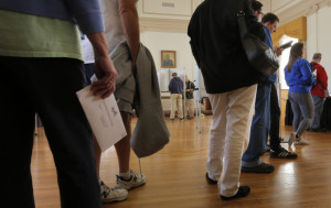 Voters wait in line as others cast their ballots at Portland City Hall on Tuesday, the first day of early voting for the Nov. 8 elections.