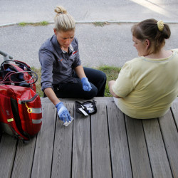 Daphne Russell, a community paramedic in Lewiston, meets with 36-year-old patient Keri Smith on the steps outside Smith's home.