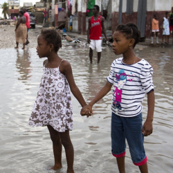 Girls wade through a street in Les Cayes, Haiti, flooded by Hurricane Matthew. A Maine relief group says it is well-positioned to help.