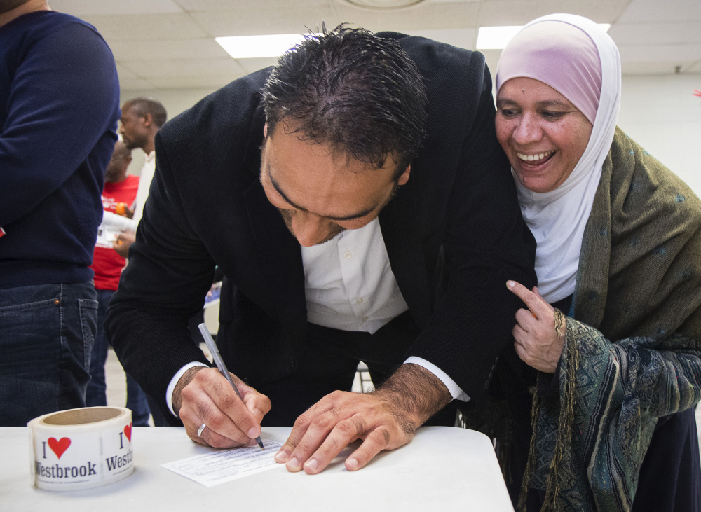 Zaineb Marwan jokes with her brother Abbas as he registers to vote in Westbrook.