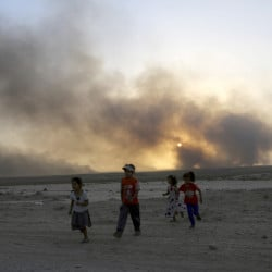 Smoke rises as children flee their homes during clashes between Iraqi security forces and members of the Islamic State group in Mosul, Iraq, on Wednesday. A senior Iraqi general on Wednesday called on Iraqis fighting for the Islamic State group in Mosul to surrender as a wide-scale operation to retake the militant-held city entered its third day.
