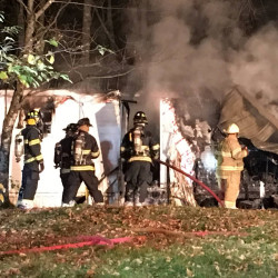 Firefighters work to extinguish a fire at a mobile home in Winthrop early Thursday morning.