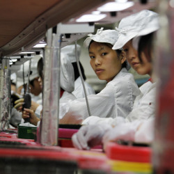 Workers for the global electronics manufacturer Foxconn, Apple's main supplier of iPhones, are seen inside a factory in Longhua, China, in 2010. Making iPhones in the United States would add $50 to $100 to the cost of each one.