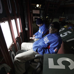 Fred Washington, right, and Brian Helmus look out to the field from inside of the scoreboard at Wrigley Field during a game earlier this season. Washington, who has worked Wrigley's scoreboard since 1990, is retiring after the season.