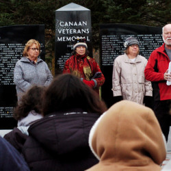Veterans committee member Dale Burrill, in red jacket, speaks Sunday during the memorial dedication in Canaan.