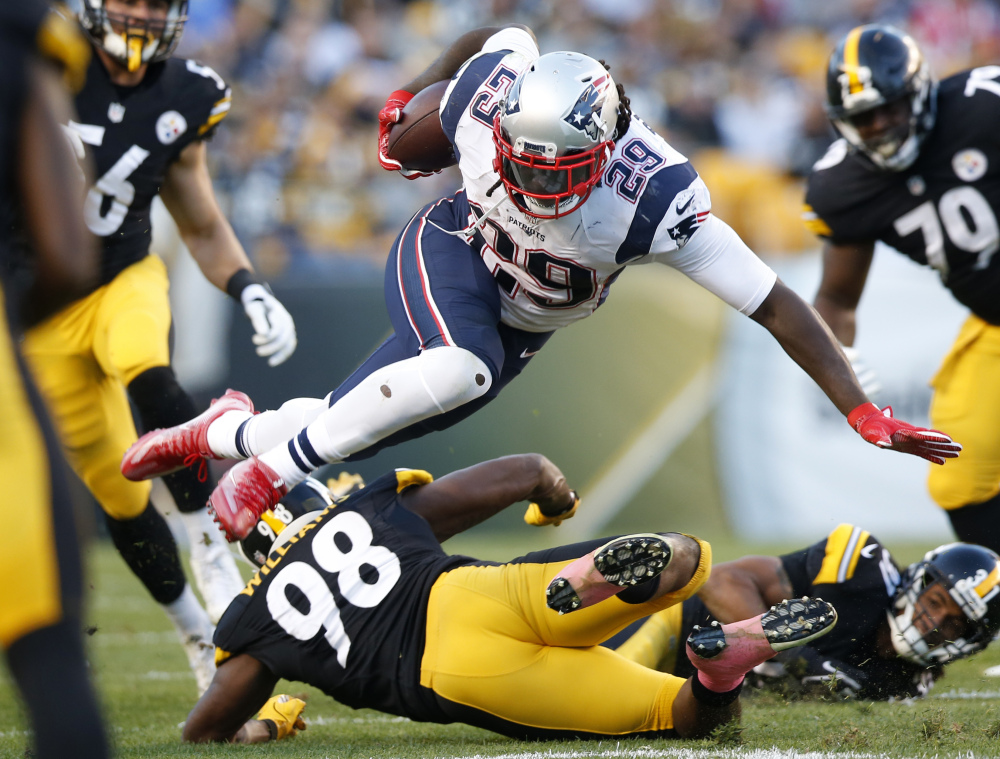 New England Patriots running back LeGarrette Blount is upended by Steelers inside linebacker Vince Williams during the first half in Pittsburgh on Sunday.