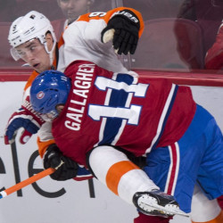 Philadelphia's Ivan Provorov is checked into the boards by Montreal's Brendan Gallagher during a 3-1 win by the Canadiens at Montreal on Monday.