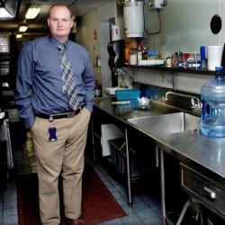 Benton Elementary School Principal Brian Wedge stands beside the school cafeteria kitchen sink on Tuesday, where exceptionally high levels of lead were detected recently. More tests are being conducted this week.