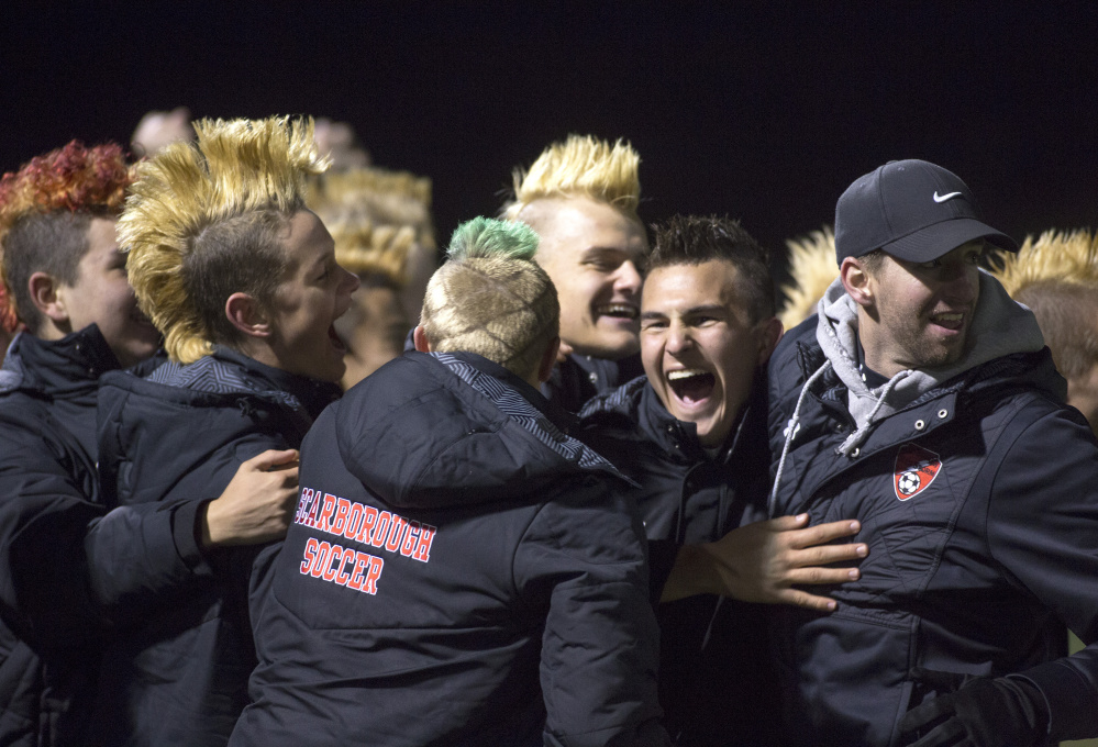 Scarborough players and coaches celebrate after the Red Storm scored late in the second half of their 1-0 victory over South Portland on Tuesday night at Scarborough High. (Photo by Brianna Soukup/Staff Photographer)