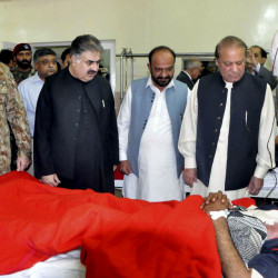 In this photo provided by Pakistan's Press Information Department, Pakistan's Prime Minister Nawaz Sharif, right, talks to a survivor of an overnight attack on the Police Training Academy, with Pakistan army chief Gen. Raheel Sharif, left, at a local hospital in Quetta, Pakistan, Tuesday, Oct. 25, 2016. Militants wearing suicide vests stormed a Pakistani police academy in the southwestern city of Quetta overnight, killing dozens of people, mostly police cadets and recruits, and waging a ferocious gun battle with troops that lasted into early hours Tuesday. (AP Photo/Press Information Department)