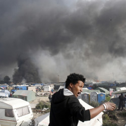 "A migrant reacts as smoke billows from burning shelters set on fire in the makeshift migrant camp known as ""the jungle"" near Calais, northern France, Wednesday, Oct. 26, 2016. Firefighters have doused several dozen fires set by migrants as they left the makeshift camp where they have been living near the northern French city of Calais. (AP Photo/Thibault Camus)"