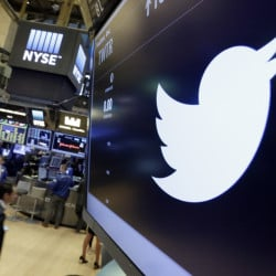 The Twitter symbol appears above a trading post on the floor of the New York Stock Exchange in July. Twitter, seemingly unable to find a buyer and losing money, is cutting about 9 percent of its employees worldwide.