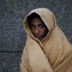 "An Eritrean migrant forced from ""the jungle"" in northern France waits for transport to a new home now that the camp has been razed."