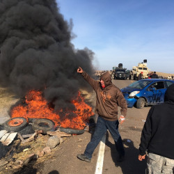 Demonstrators stand next to burning tires as armed soldiers and law enforcement officers assemble Thursday to force Dakota Access pipeline protesters off private land where they had camped to block construction. The pipeline is to carry oil from western North Dakota through South Dakota and Iowa to a pipeline in Patoka, Ill.