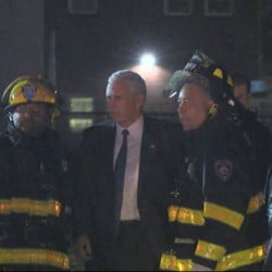 Republican vice presidential candidate Mike Pence talks with firefighters at New York's LaGuardia Airport on Thursday night after his campaign plane slide off the runway while landing.