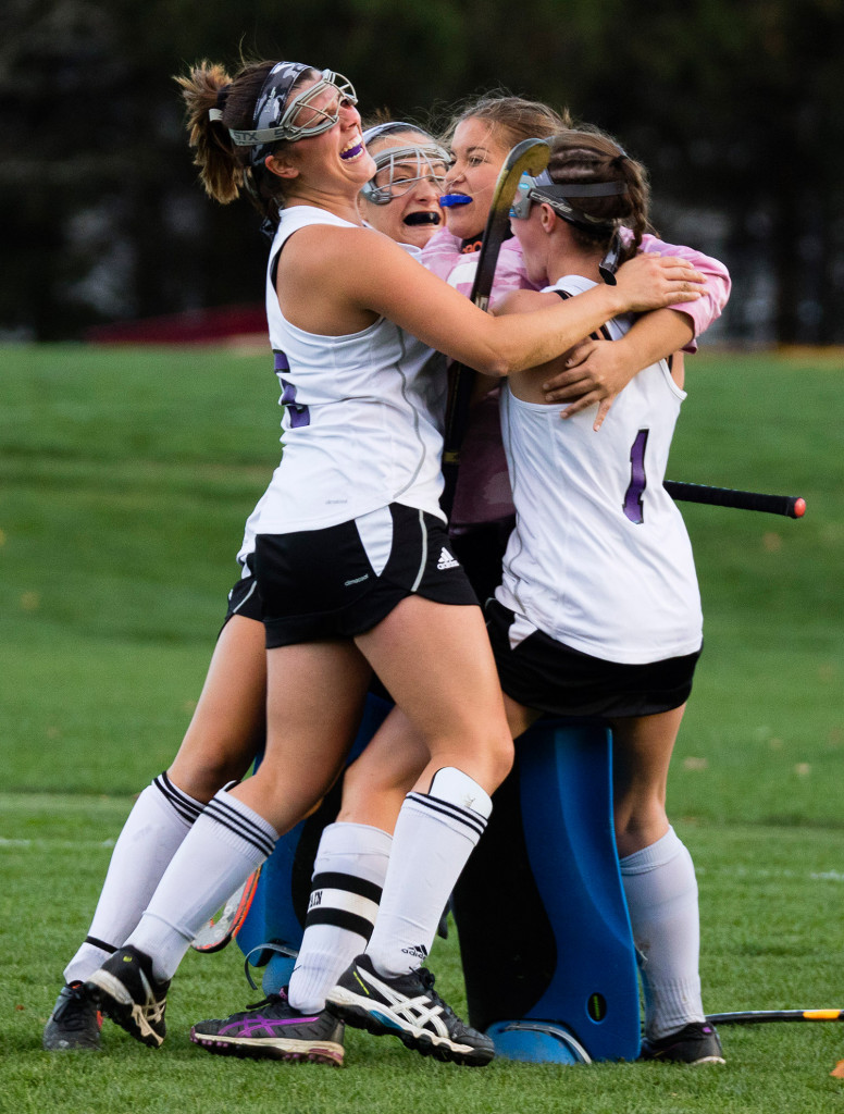 Marshwood players including Madison Paulin, left, and Hannah Costin, right, embrace goalie Shannon Giblin as they celebrate their semifinal win over Scarborough on Monday in South Berwick.