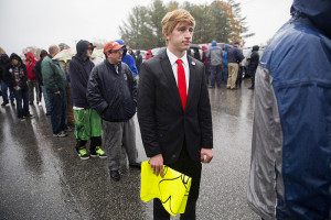 Jonathan Pozzi, from Wilmington, Mass. waits in the rain dressed up as Donald Trump before Trump's rally at the Christian Open Door Academy.