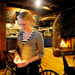 "Desiree Cofran lights candles for tables before dinner Wednesday at Boone's Fish House & Oyster Room in Portland. She says she would quit if her employer eliminated tipping. ""It would be a huge pay cut for me."" Shawn Patrick Ouellette/Staff Photographer"