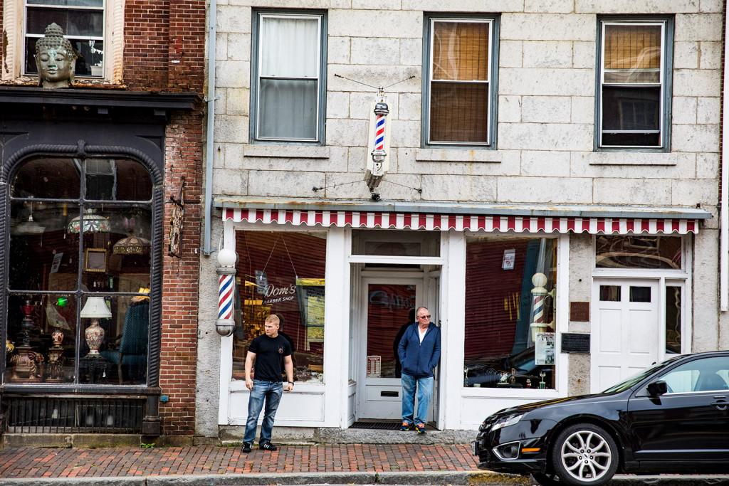 Folson, of Randolph, wait to get their hair cut at Doms Barber Shop ...