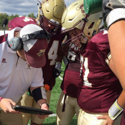 Thornton Academy offensive and defensive line coach Nick Tabor uses a tablet displaying video replays to (from left) Jack Webb, Kyle Holman and Jerry Nason during a game this season. Courtesy Thornton Academy
