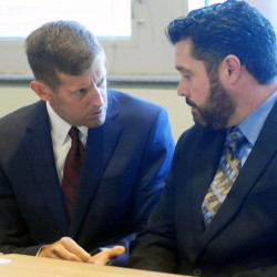 Bryan Carrier, right, and his attorney, Walt McKee, confer during a hearing Sept. 26 in Augusta at the Bureau of Motor Vehicles, where Carrier asked to have his drivers license restored. Andy Molloy/Kennebec Journal
