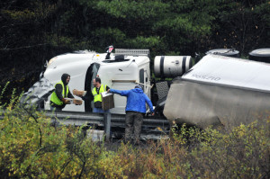 Staff photo by Joe Phelan Workers transfer mail from an overturned tractor-trailer to another truck near mile 114 of Interstate 95 northbound on Friday in Augusta.