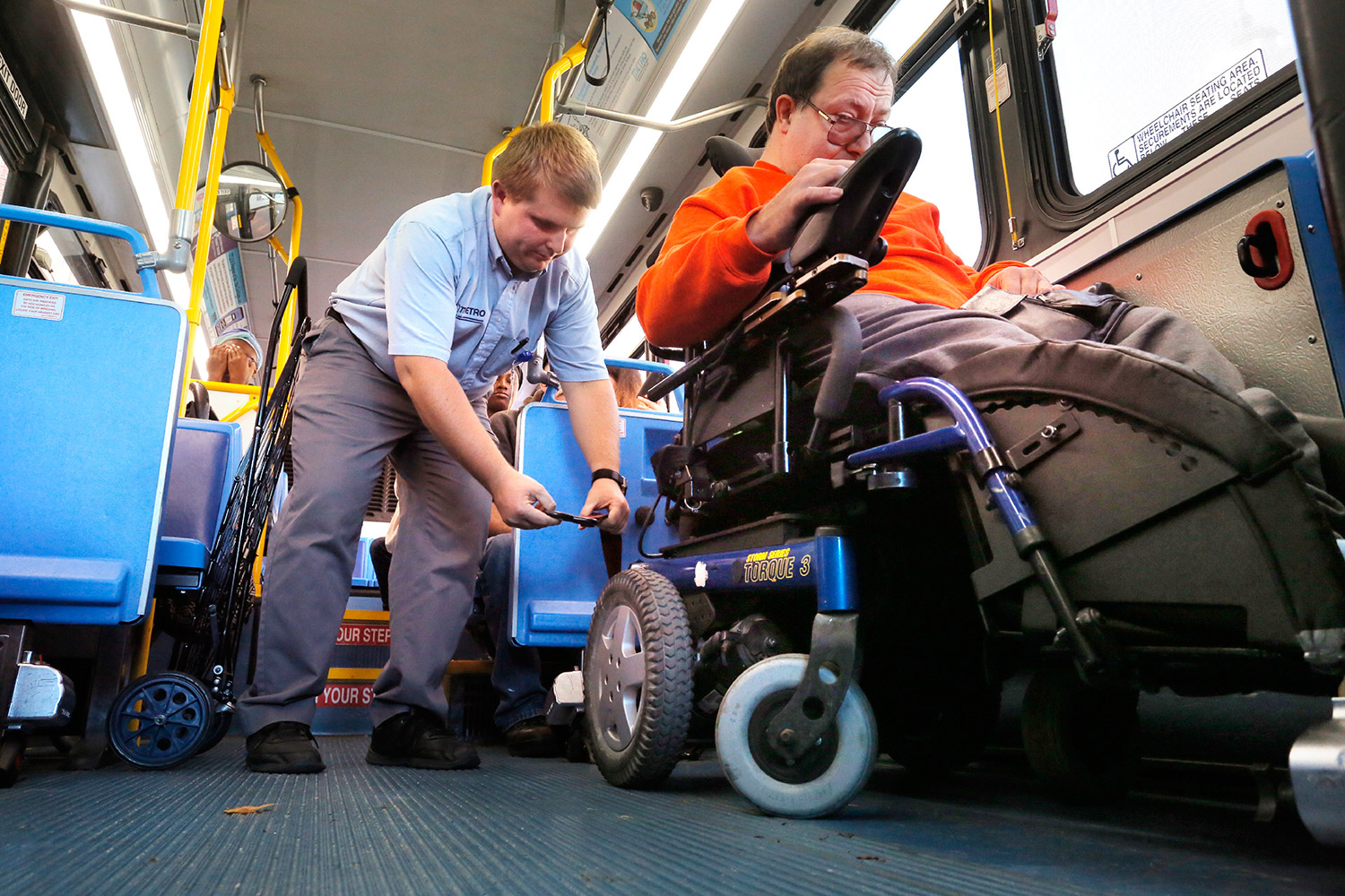 Metro bus driver Mark Shapp fastens a strap to secure Joe Kilbride's wheelchair while driving route 9B in Portland.