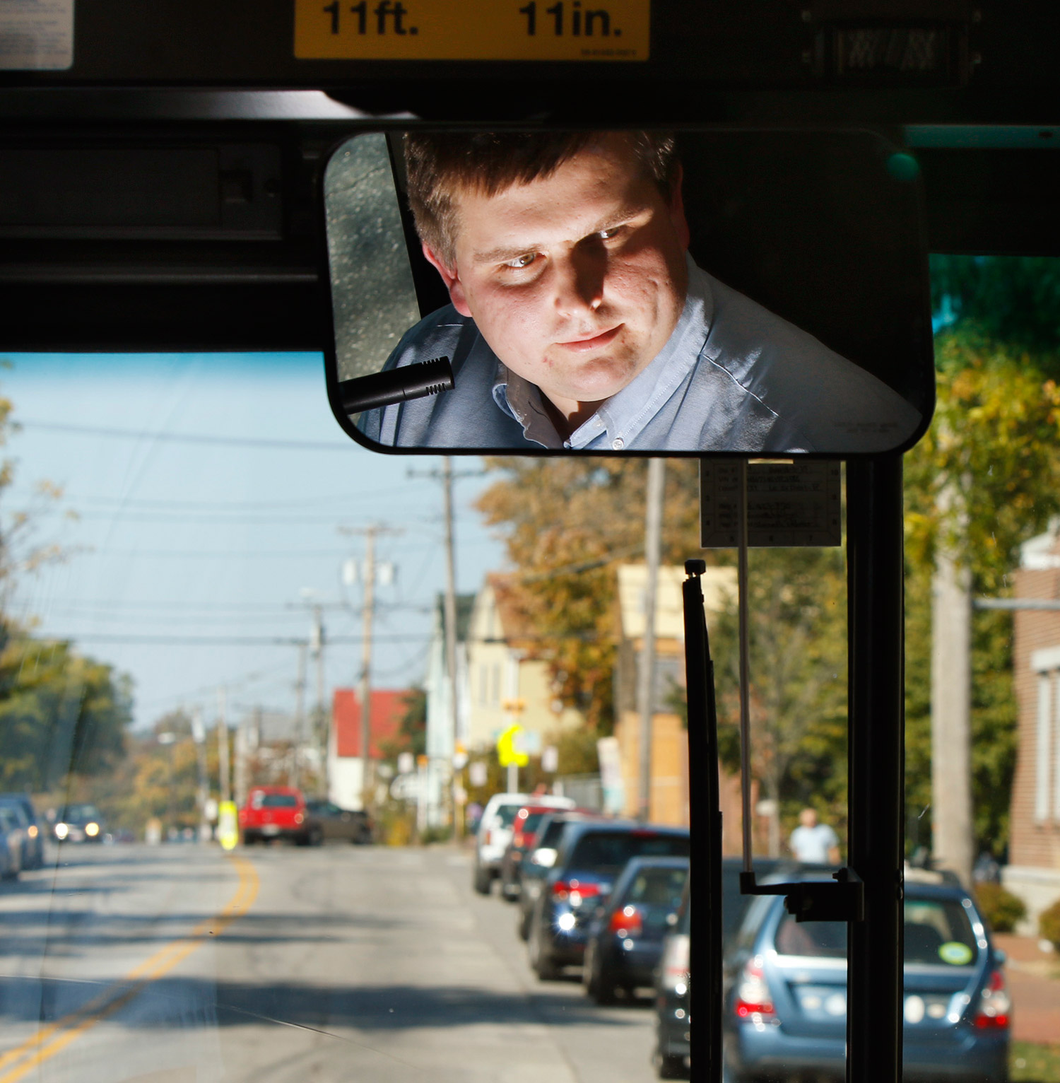 Metro bus driver Mark Shapp is reflected in a mirror of a bus while driving Route 9B in Portland.
