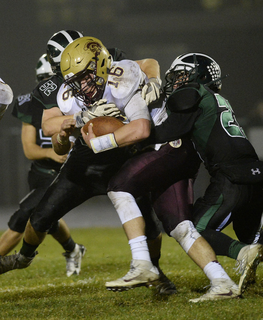 Thornton Academy's Michael Laverriere drives for yardage as Bonny Eagle's Aaran Hodgman, left, and Keith Hoffses try and bring him down.