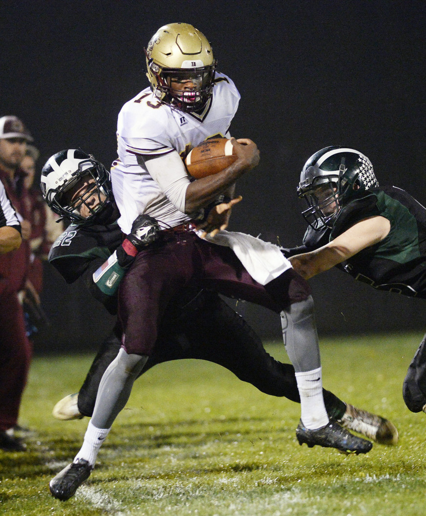 Bonny Eagle's Keith Hoffses, left and Christian Napolitano push Thornton Academy's Johnny Rosario out of bounds on Friday.