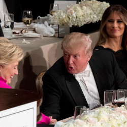 Republican presidential candidate Donald Trump, center, accompanied by his wife Melania Trump, right, shakes hands with Democratic presidential candidate Hillary Clinton at the 71st annual Alfred E. Smith Memorial Foundation Dinner on Oct. 20 in New York. The dinner is supposed to be a gentle roast at which political foes parry a bit but always with rubber rapiers.