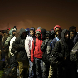 "Migrants line up to register at a processing center in the makeshift migrant camp known as ""The Jungle"" near Calais, northern France, Monday. French authorities say the closure of the slum-like camp will last approximatively a week in what they describe as a ""humanitarian"" operation.  Associated Press/Emilio Morenatti"