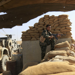 An Kurdish Peshmerga fighter stands guard outside Bartella, Iraq, Friday. Bartella is a historically Christian town about 9 miles  from Mosul's outskirts. Associated Press/Khalid Mohammed
