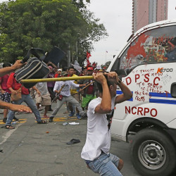 Protesters hit a Philippine National Police van after it rammed into the crowd outside the U.S. Embassy in Manila, injuring an undetermined number of people Wednesday. Associated Press/Bullit Marquez
