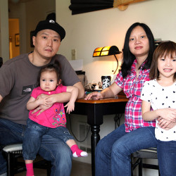 Korean adoptee Adam Crapser, left, poses with daughters, Christal, 1, Christina, 5, and his wife, Anh Nguyen, in the family's living room in Vancouver, Wash. in 2015.